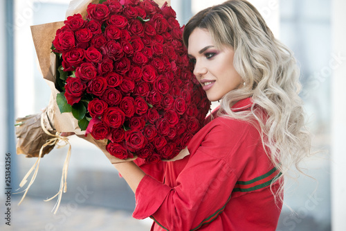 Photo  Elegant beautiful blonde woman is wearing green fashion dress in cafe holding with big bouquet of 101 red roses