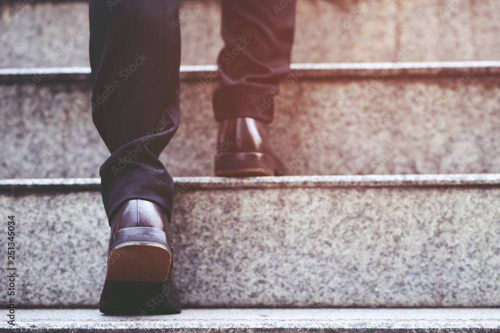 Fototapeta modern businessman working  close-up legs walking up the stairs in modern city. in rush hour to work in office a hurry. During the first morning of work. stairway. soft focus.