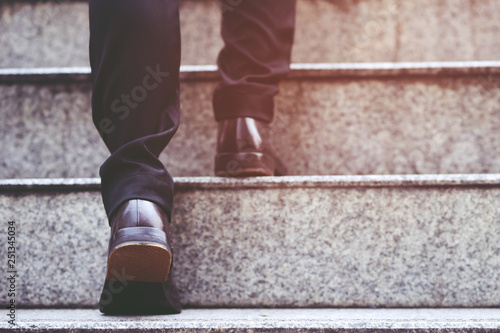 Fotografia  modern businessman working  close-up legs walking up the stairs in modern city