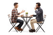 Young guy in a cafe talking to a bearded man drinking coffee