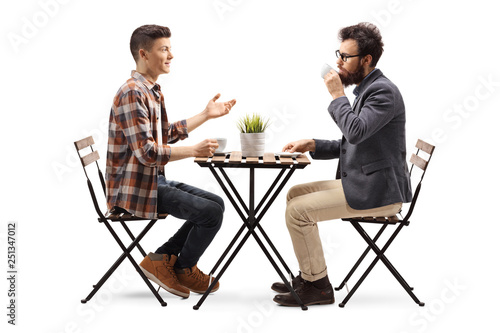 Fotografía  Young guy in a cafe talking to a bearded man drinking coffee
