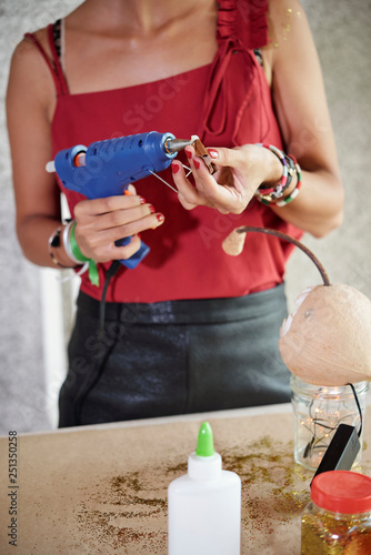 Woman working with electric glue gun Canvas Print