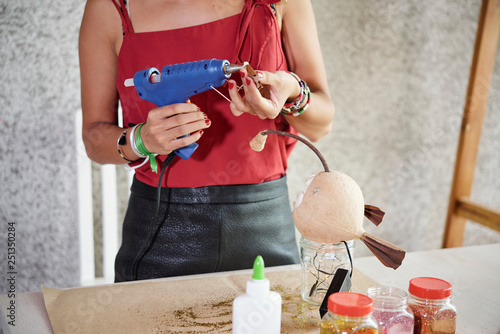 Woman using electric glue gun for work Wallpaper Mural
