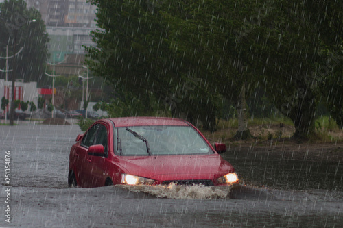 Canvas Print Red car rides in heavy rain on a flooded road
