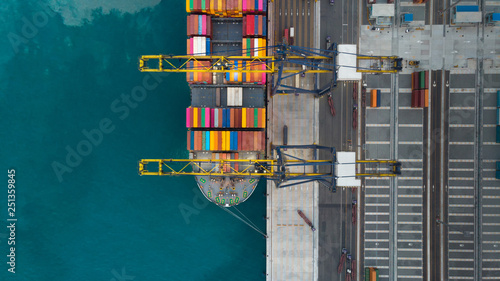 Fototapeta Aerial of cargo ship carrying container and running for export  goods  from  cargo yard port to other ocean concept freight shipping ship on blue sea