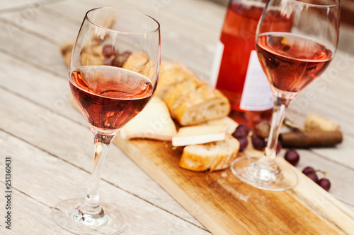 Obraz na płótnie Two glasses of rose wine and board with fruits, bread and cheese on wooden table