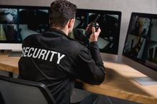 Rear View Of Guard In Uniform Talking On Walkie-talkie