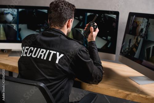 Fotografía  rear view of guard in uniform talking on walkie-talkie