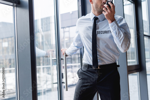 Fototapety, obrazy: cropped view of handsome guard in suit talking on walkie-talkie