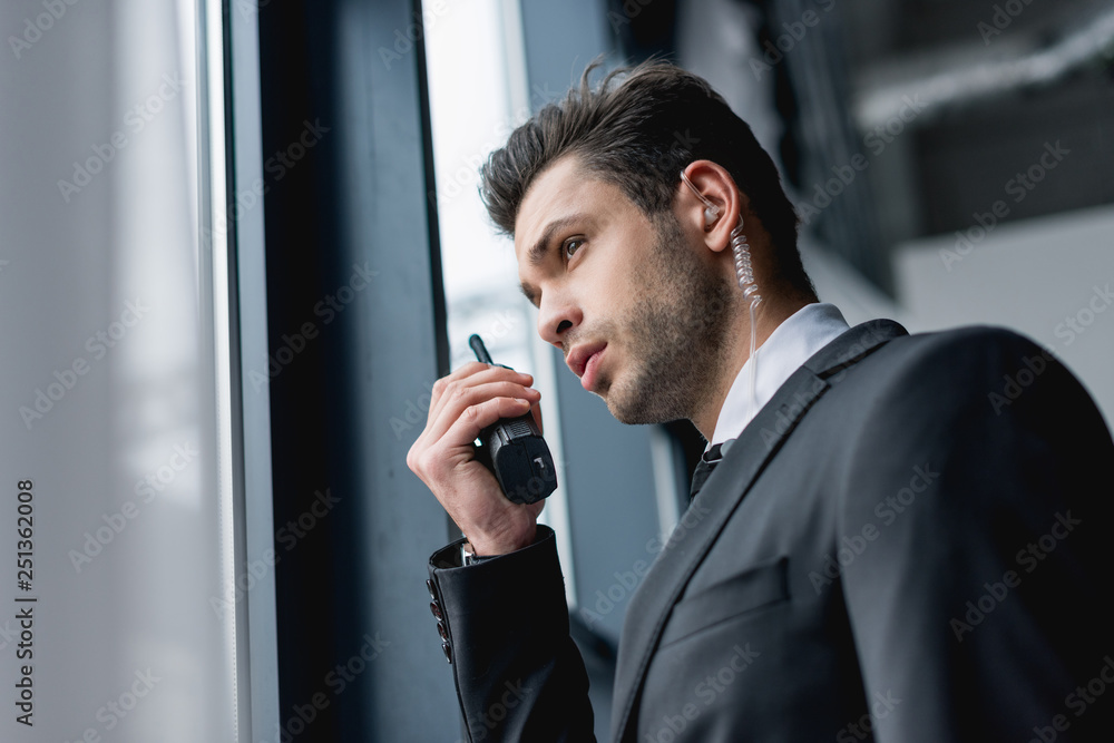Fototapeta handsome bodyguard in suit using walkie-talkie