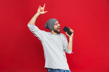 Image Of Optimistic Man 30s Singing While Listening To Music With Earphones And Mobile Phone, Isolated Over Red Background