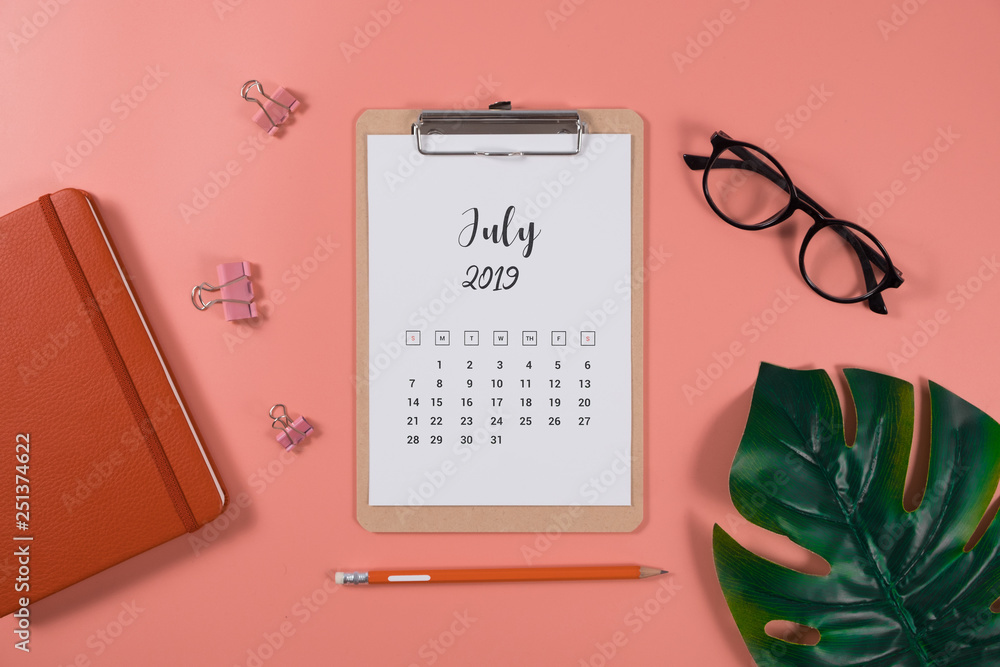 Fototapety, obrazy: Flat lay calendar with clipboard, palm leaves and pencil on living coral color background. July 2019. top view.