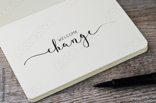 Fototapeta WELCOME CHANGE hand lettering in notebook with pen on wooden background