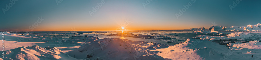 Fototapety, obrazy: Bright colorful sunset panorama view in Antarctica. Orange sun lights over the snow covered polar surface. Picturesque winter landscape. The beauty of the wild untouched Antarctic nature.