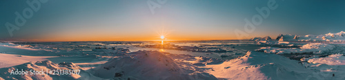 Bright colorful sunset panorama view in Antarctica. Orange sun lights over the snow covered polar surface. Picturesque winter landscape. The beauty of the wild untouched Antarctic nature.