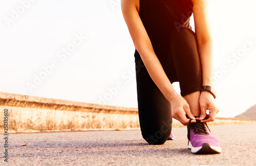 Fotografía  sport woman tying shoelace while running, sunset on the long road