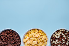 Cereals Bowl With Chocolate Balls, Rings And Yellow Corn Flakes For Dry Breakfast On Blue Background. Copy Space, Top View