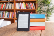 Digital E-book Reader And Paper Books On Table