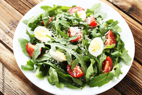 Salad with arugula leafs, tomatoes and eggs on brown wooden table Canvas Print