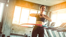 Woman Doing Exercises With Hula Hoop In Gym.