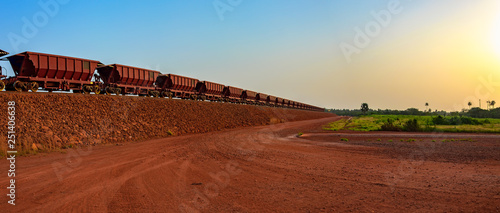 Railway carriages for transportation of bauxite ore on train tracks at the end of the railway line from bauxite mining Canvas Print
