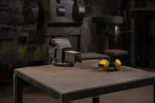 Industrial Mechanical Cast Iron Vice Bolted To A Metal Work Station Table In A Dark Traditional Old Style Repair Workshop Next To Yellow Ear Defenders