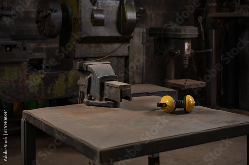 Photo Industrial mechanical cast iron vice bolted to a metal work station table in a d