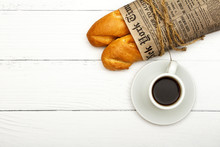 A Cup Of Coffee, Fresh Bread, Toast On A White Woody Background. Morning Breakfast Fresh Bread With A Cup Of Coffee. View From Above.