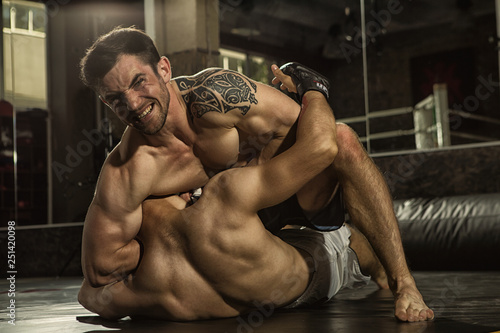 Photo  Two MMA fighters grappling on training in gym