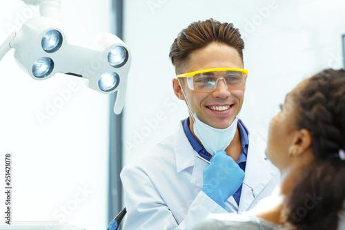 Fotografie, Obraz  Young male dentist smiling to patient, taking off his medical mask