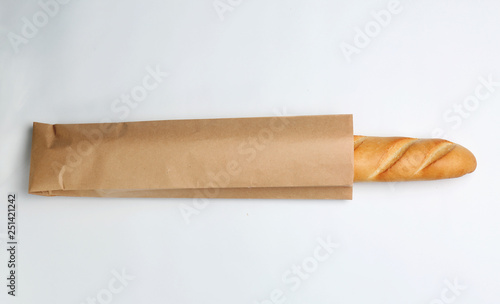 Fototapeta Paper bag with baguette on white background, top view. Space for design obraz