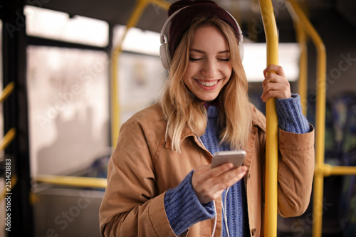 Young woman with headphones listening to music in public transport - 251421883