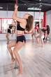 Sexy young women practicing pole dancing in fitness studio