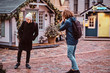 A young curly photographer with a backpack makes a photo of a friend on the market of the Old City square decorated with festive decorations