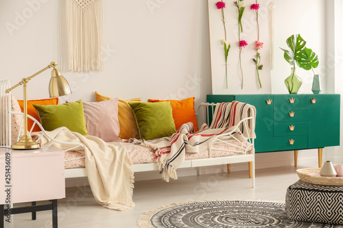 Olive green, pastel pink, yellow and orange pillows on ...