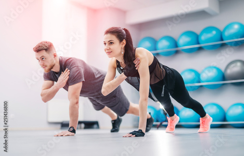 Fotografia  Pretty young couple doing exercises together in the light gym