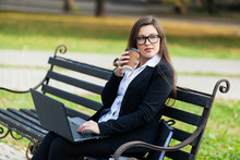 Business Woman Sitting In The Park On A Bench, Working With A Laptop