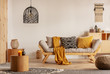Leinwanddruck Bild - Scandinavian sofa with pillows and dark yellow blanket in bright living room interior with black chandelier