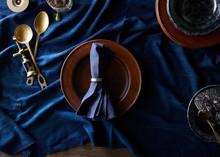 Indigo Linen, Brass Servers, And Wooden Plates