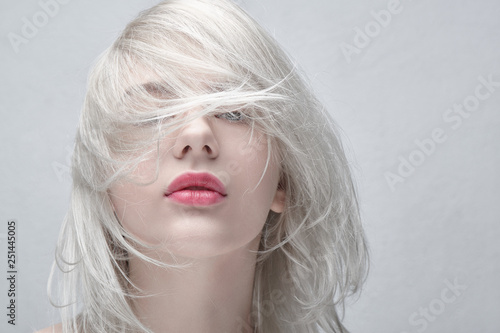 Recess Fitting Hair Salon Portrait of a young beautiful blonde woman with plump red lips on a white background close up. Fashionable fancy hairstyle