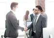 Successful managers shaking hands after closing deal in office