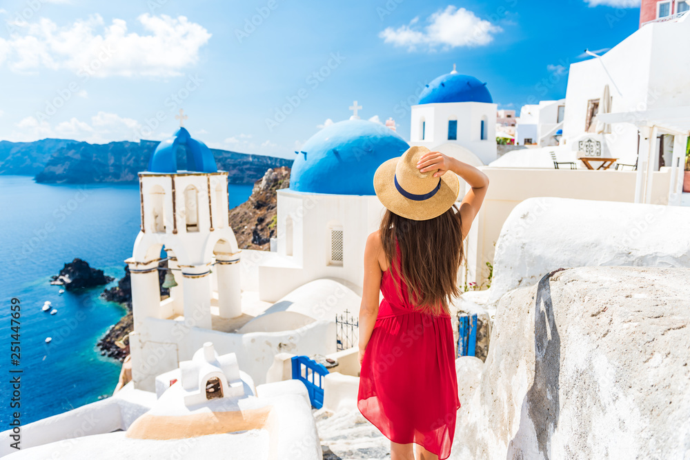 Fototapeta Luxury travel vacation Europe holiday Santorini girl in hat and red fashion dress walking 3 blue domes famous tourist attraction. Summer sun holidays adventure.
