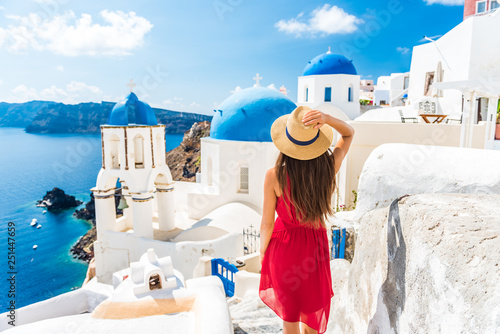 Fototapeta Luxury travel vacation Europe holiday Santorini girl in hat and red fashion dress walking 3 blue domes famous tourist attraction. Summer sun holidays adventure. obraz