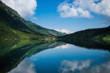 Scenic view of calm Morskie Oko lake by Tatra Mountains against blue sky