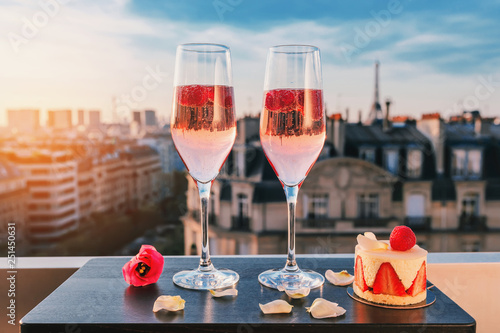 Poster Paris Paris luxury lifestyle. Pink champagne in two glasses, traditional french cake with strawberries on a balcony on the sunset