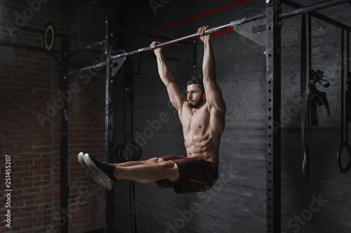 Fotografiet  Crossfit athlete doing abs exercise on horizontal bar at the gym