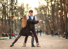 Elegant Young Couple In Love In Classic Style Passionately Dancing In City Park