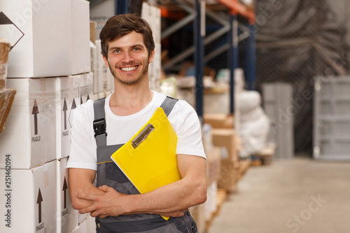 Worker wearing uniform and white t shirt, holding yellow clipboard. Handsome man smiling, standing and leaning on white boxes in warehouse. Concept of entrepot and commercial industry.