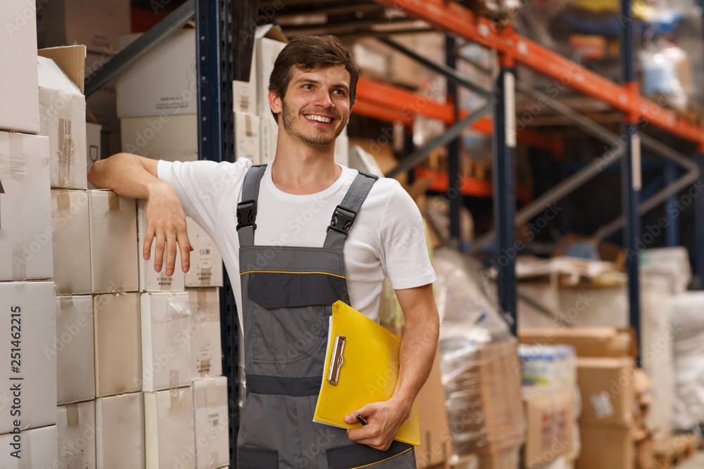 Fototapeta Cheerful worker wearing uniform and white t shirt, holding yellow clipboard. Handsome man smiling, standing and leaning on white boxes in warehouse. Concept of entrepot and commercial industry.