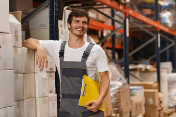 FototapetaCheerful worker wearing uniform and white t shirt, holding yellow clipboard. Handsome man smiling, standing and leaning on white boxes in warehouse. Concept of entrepot and commercial industry.